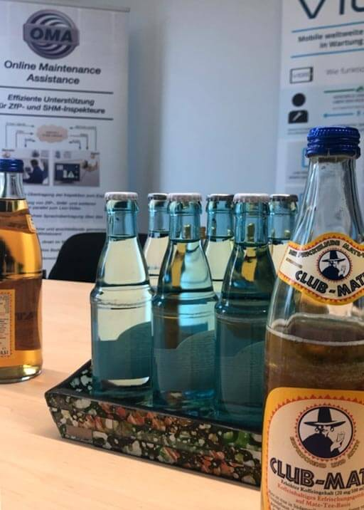 Im Konferenzraum von Bitnamic stehen Wasser und Mate-Tee auf dem Tisch.