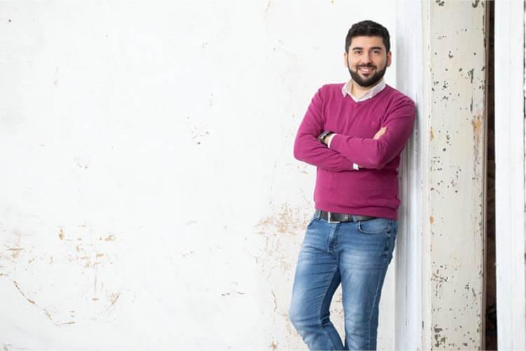 Bilal Erkin, der Gründer von Erkin Digital, lehnt an einer Wand.